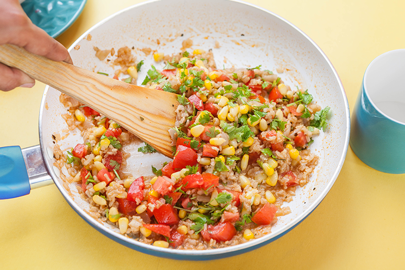 Remove from the heat, and throw in some tomato, corn and coriander. Make sure to stir them well.