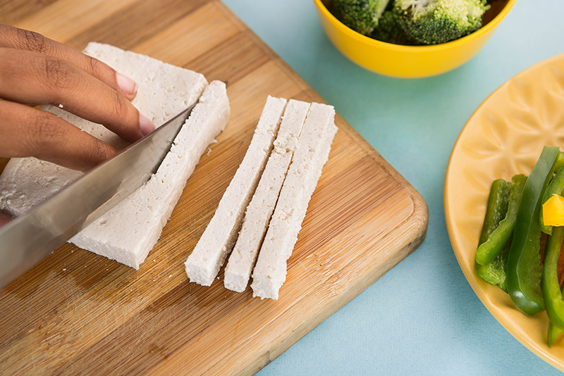 Now let's begin by cutting the tofu into ½-inch thin slices and placing them in a plate.