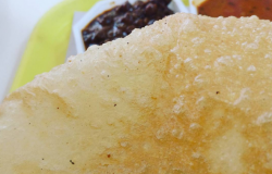 <p>Well, it's a tad dangerous but a drop of vinegar to the oil definitely puffs up the poori.</p>